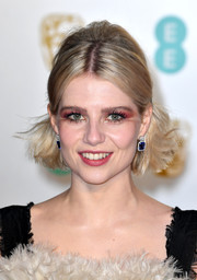 Lucy Boynton styled her hair into a half updo with a teased crown for the EE British Academy Film Awards.