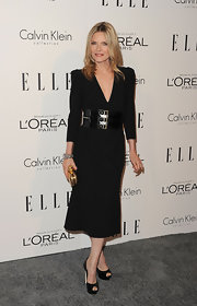 Michelle Pfeiffer added a golden touch to her belted black dress with a gold box clutch at the 'Elle' Women in Hollywood Tribute.