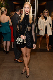 Poppy Delevingne flashed some skin in a sheer black ruffle-front blouse during the Elle Women in Hollywood celebration.