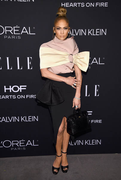 Jennifer Lopez attended the 2018 Elle Women in Hollywood celebration wearing an asymmetrical pink top, which she styled with a champagne shoulder band, both by Maticevski.