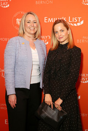 Mena Suvari attended the Emily's List pre-Oscars brunch carrying a perforated black leather clutch.