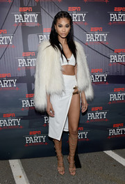 Chanel Iman toned down her barely-there attire with a white fur jacket.