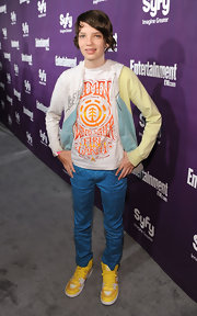 Kodi Smit-McPhee, at the EW and Syfy party during Comic-Con 2010, sported a pair of yellow-and-white Nike high top sneakers with yellow laces.