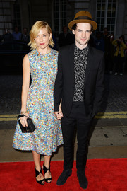 For her bag, Sienna Miller picked a black Christopher Kane safety-buckle leather purse.
