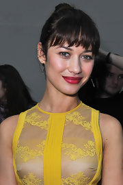 Olga Kurylenko wore her hair in a high classic bun with choppy brow-grazing bangs at the Elie Saab fashion show in Paris.