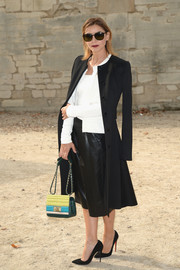 Clotilde Courau looked flawlessly put together in a vintage-chic black coat layered over a white cardigan and a leather skirt during the Elie Saab fashion show.