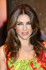 Elizabeth Hurley launched her new collection of bed linens wearing her wavy layered hair with a sexy slightly off-center part.