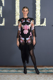 Angela Lindvall donned a cocktail dress, featuring an ultra-feminine blend of lace, orchids, and ruffles, for the Elle anniversary celebration.
