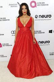 Kim Kardashian was smoking hot in a low-cut red empire gown by Celia Kritharioti during the Elton John AIDS Foundation Oscar viewing party.