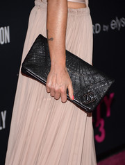 Laeticia Hallyday paired her Grecian dress with a textured black leather clutch by Chanel when she attended the Pink Party.