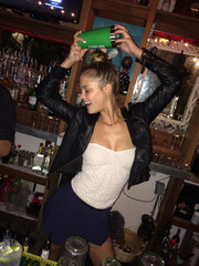 Nina Agdal teamed a white tube top with a blue mini and a leather jacket for a night out in Miami Beach.