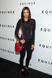 Nina Dobrev added a punch of color with a red heart-shaped bag by Donatienne.