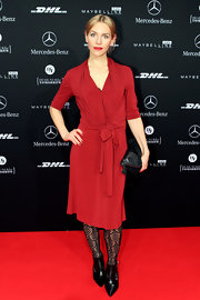 Julia Dietze wore this red knit dress with black accessories to the Escada show in Berlin.