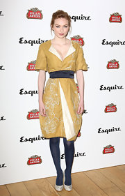 Eleanor Tomlinson chose a mustard yellow dress with white floral embroidery and a dark blue sash for her look at the Esquire summer party in London.