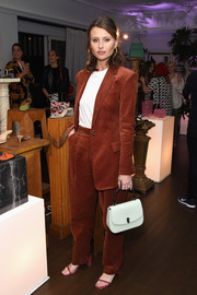 Alyson Michalka completed her ensemble with a white Edie Parker mini tote.