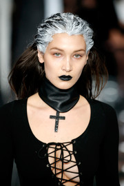 A broad black leather choker with a cross pendant finished off Bella Hadid's look.