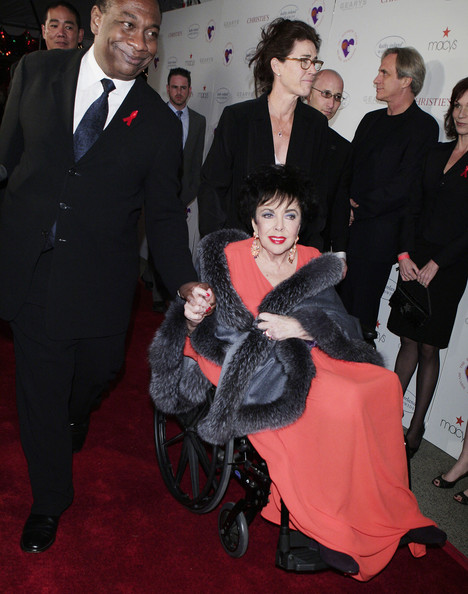 Elizabeth Taylor paired a gray fur scarf with her coral dress for a glam finish.