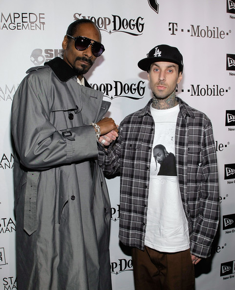 Snoop's looking dapper in a gray trench coat and oversized aviator shades,