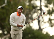 Tiger paired this nude v-neck sweater over an orange polo for a muted course-look.