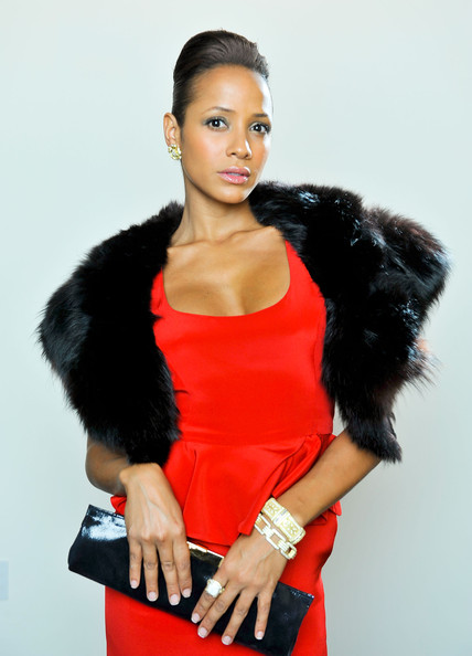 She is modeling a long black clutch. The fur and the clutch give this look a classic finish.