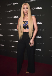 Iggy Azalea rocked a tiny plaid crop-top at the Fashion Nova x Cardi B collaboration launch.