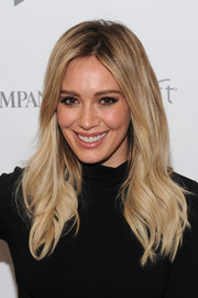 Hilary Duff styles her hair in a middle-part with long, flowing waves that brush over her shoulders for a beachy look.