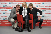 Olivia Newton-John left her leather bag on the floor as she posed with 'A Few Best Man' co-stars at the Rome Film Fest.