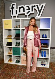 Chrissy Teigen teamed her jacket with a pair of high-waisted trousers in a lighter shade of pink.