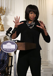The FLOTUS Michelle Obama paired a multi-beaded necklace with a black outfit to add some color and flavor to her look.