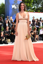 Rebecca Hall styled her gown with a gold sequin clutch.