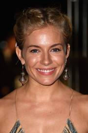 Sienna Miller spiced up her look with a pair of geometric earrings when she attended the 'Foxcatcher' premiere in London.