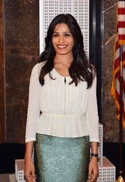 Freida Pinto chose an elegant white peplum top and a blue jacquard skirt for her visit to the Empire State Building.