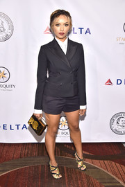 Kat Graham styled her suit with black and gold strappy heels.