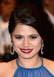 Melonie Diaz chose a deep blood red lipstick for her glam beauty look.