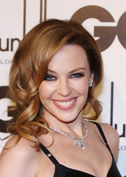 Kylie Minogue rocked lustrous shades of shadow and a set of long lashes at the GQ Men of the Year Awards. To try her look at home, sweep a shimmering shadow across the lids, line inner and outer lash lines with a black liner and apply false lashes on upper lash lines. To finish the look, add a few coats of black mascara.
