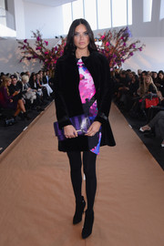 Adding an extra pop of color to her dress, Adriana Lima accessorized with a purple and black print clutch.