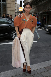 Miroslava Duma teamed her crop-top with a pair of tapered white and brown slacks.