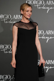 Uma Thurman paired a black leather clutch with a sheer-panel dress for the Giorgio Armani Cruise 2020 show.