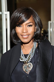 Angela Bassett arrived at the Giorgio Armani Madison Avenue event looking flawless. Her hair, shiny and sexy, was straight with lots of swing. To recreate her look, smooth hair with either a flat iron or blow-dry tresses with a round brush. Flat-ironed hair might need a little bend at the ends with a large-barreled curling iron.