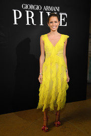 Helena Bordon floated into the Armani Prive show in a yellow lace ruffle dress by Blumarine.