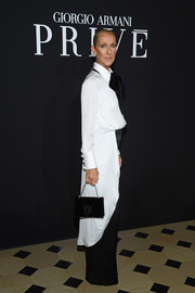 Celine Dion accessorized with a black velvet purse by Giorgio Armani at the Armani Prive fashion show.