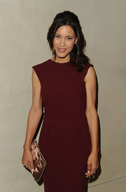 Julia Jones paired her burgundy sheath dress with a satin clutch.