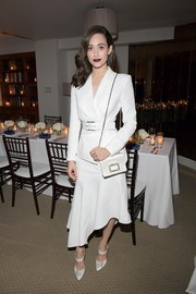 Emmy Rossum looked perfectly polished in a white asymmetrical-hem skirt suit by Michael Kors at the Stuart Weitzman Beverly Hills boutique opening.