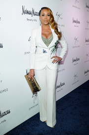 Vivica A. Fox bared her cleavage in a fitted white pantsuit at the Giuseppe for Jennifer Lopez launch.