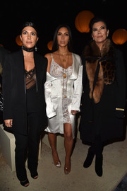Kourtney Kardashian contrasted her sister's sexy style with a mannish coat and pants combo during the Givenchy fashion show.