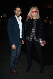 Amanda Lear looked youthful and edgy in a black moto jacket and a pair of skinnies at the Givenchy fashion show.
