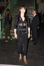 Juliette Binoche looked ageless at the Givenchy fashion show in a high-slit tux-style skirt suit teamed with a sheer blouse.