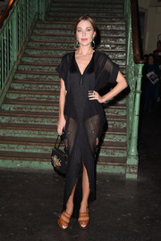 Ulyana Sergeenko looked sultry in a fringed black mesh dress during the Givenchy fashion show.