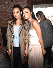 Jamie Chung attended the Glam App's Glamchella wearing a stylish tan trenchcoat with black piping.