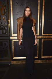 Irina Shayk joined the Gold Obsession Party wearing a simple black maxi dress by Alaia.
